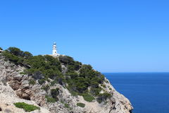 Lighthouse and mountain view  in North Mallorca. Lighthouse and Sea view in a blue sky with trees, mountains and rocks in North Mallorca Royalty Free Stock Photos