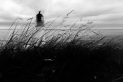 Moving grass and lighthouse in black and white. Top of Rua Reidh lighthouse with moving grass in the foreground and sea in the background, in black and white royalty free stock photos