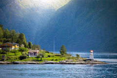 Lighthouse on a fjord shore. Lighthouse and multicolored houses on a fjord shore, norway Royalty Free Stock Images
