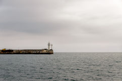 Lighthouse or navigation beacon. On the end of a harbour wall to guide or warn incoming shipping under a cloud grey sky stock photography