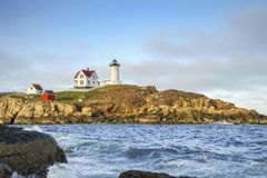 Lighthouse Guide. New England style lighthouse overcast sky in Maine. A steadfast lookout across an unpredictable ocean Royalty Free Stock Images