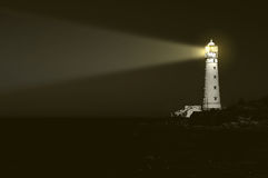 Lighthouse at night. Beam of light over sea Stock Images