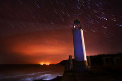 Lighthouse with night sky at background stars trai Royalty Free Stock Photos