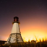 Lighthouse with night sky at background stars trails Stock Photos
