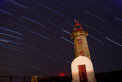 Lighthouse at night with startrails Royalty Free Stock Photos