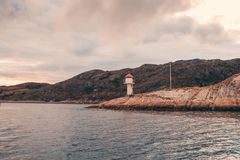 Lighthouse on Norway island with small mountains at coastline royalty free stock images