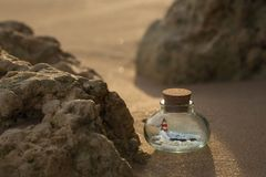 Lighthouse and ocean waves inside the bottle standing on the sand among the rocks stock photos