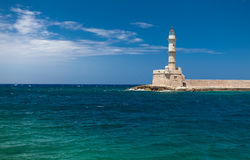 Lighthouse in the old harbor and azure sea. Royalty Free Stock Photo