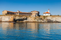 Lighthouse and old wooden buildings on Island Stock Photos