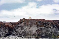 Lighthouse over basalt rocks, Heimaey Island, Iceland Stock Image