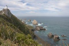 Lighthouse overlooking rocks Stock Photo