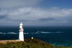 Lighthouse overlooking rough blue ocean. The 1860's vintage Cape Otway Lighthouse, Victoria, Australia, overlooking the wild Southern Ocean royalty free stock image