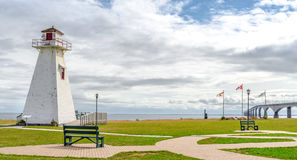 Lighthouse in the park. Warm muggy day in PEI. New Brunswick Confederation Bridge in distance. A derelict lighthouse now retired to a park by PEI to New royalty free stock image