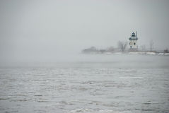 Lighthouse on a Peninsula in the Cold Fog Stock Photography