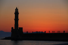 Lighthouse and people silhouettes at dusk. Chania Crete Stock Image