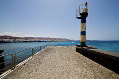 Lighthouse and pier boat in the blue sky   arrecife Stock Photography