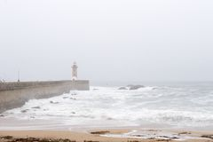 Lighthouse and pier in fog. Foggy morning with lighthouse, pier, and stormy seas. Porto, Portugal stock image