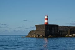 A lighthouse on a pier in Ponta Delgada. A lighthouse guiding ships into the harbour of Ponta Delgada, the capital of São Miguel, the largest island of the Royalty Free Stock Photo