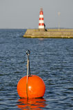Lighthouse on pier and red buoy Stock Photo