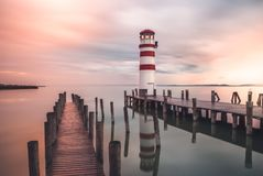 Lighthouse with a Pier at Sunrise. Lighthouse with Beautiful Pink Sky in Podersdorf at Neusiedl Lake, Austria stock photos