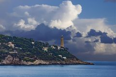Lighthouse on Point Under Storm Clouds Stock Photo