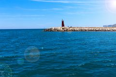 Lighthouse at the port entrance on a sunny summer day. stock photo