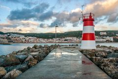 Lighthouse of the Portuguese village of Sesimbra. Lighthouse of the village of Sesimbra at sunset after a rainy day, in Portugal Royalty Free Stock Images