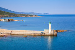 Lighthouse of Propriano port, Corsica, France. White lighthouse tower on stone pier. Entrance to Propriano port, Corsica, France Royalty Free Stock Photo