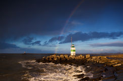 Lighthouse and rainbow over sea Stock Photo