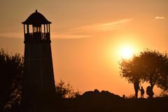 Lighthouse in the rays of sunset. Royalty Free Stock Photos