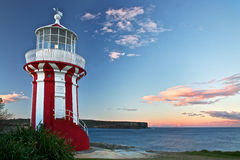 Lighthouse in red. Red and white striped lighthouse at sunset Stock Image