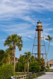 Lighthouse on Right. Sanibel, FL lighthouse  on western end of island against sky to the right in image with palm trees Stock Photo