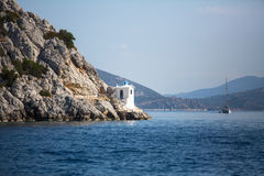 Lighthouse on rocks in the Aegean sea Stock Image