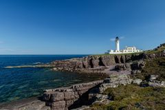 Lighthouse on rocks with blue sky and sea. Rua Reidh Lighthouse with keepers house on a rocky coastline with blue sky royalty free stock image