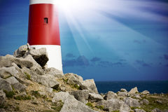Lighthouse on rocks with light beams Royalty Free Stock Photos