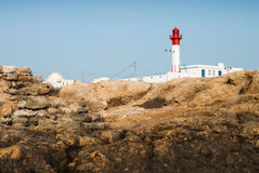 Lighthouse on the rocks Stock Images