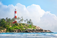 Lighthouse on the rocks. Near the ocean at blue sky with big white clouds in Kovalam, Kerala, India stock photography