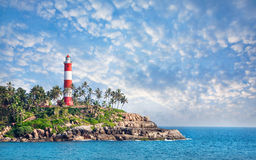 Lighthouse on the rocks. Near the ocean at blue sky with clouds in Kovalam, Kerala, India royalty free stock photos