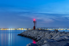 Lighthouse and rocks night seascape. City lights after sunset. Stock Photo