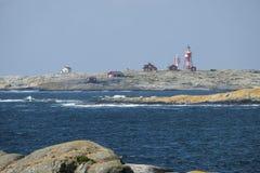 Lighthouse on rocks off the coast stock image