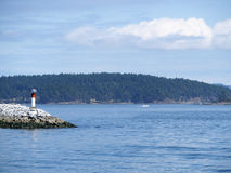 Lighthouse on the rocks on a sunny day. Pretty lighthouse on vancouver island to help the boats on the foggy mornings Royalty Free Stock Image