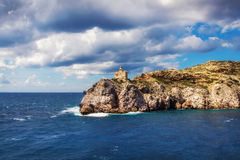 Lighthouse on the rocky Aegean shore Royalty Free Stock Image