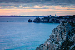 Lighthouse on Rocky Cliff. Lighthouse at night during sunset on a rocky cliff in Camaret-sur-Mer France royalty free stock photo