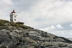 Lighthouse on a rocky cliff Stock Photography
