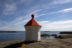 Lighthouse on rocky coast Royalty Free Stock Image