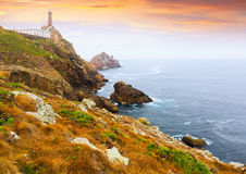 Lighthouse on  rocky coast Stock Photography