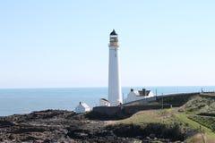 Lighthouse on a rocky headland Royalty Free Stock Photos