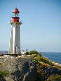 Lighthouse and rocky shoreline Stock Photos