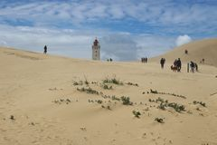 The lighthouse Rubjerg Knude fyr, Denmark, northwest coast. LONSTRUP, DENMARK - JULY 7, 2016: Visitors of the Lighthouse Rubjerg Knude fyr walk over a huge sand Stock Photo