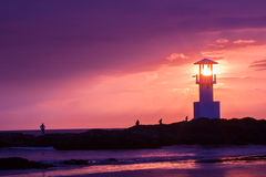 Lighthouse s. Earchlight beam through marine at sunset Royalty Free Stock Photography